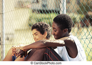Friendship - Two young African boy resting outdoors on a...