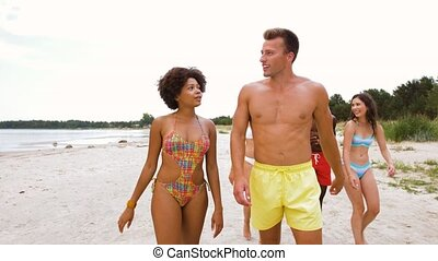 mixed race couple walking along beach with friends -...