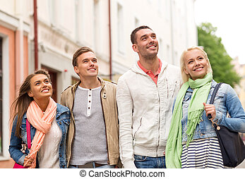group of smiling friends walking in the city
