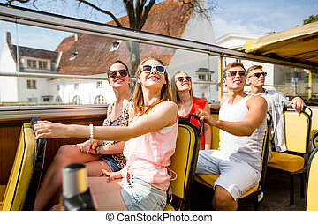 group of smiling friends traveling by tour bus - friendship...