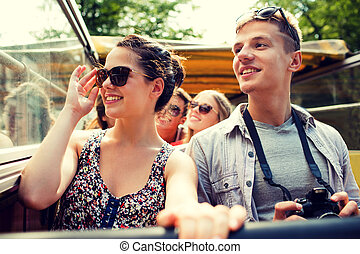 smiling couple with camera traveling by tour bus - ...