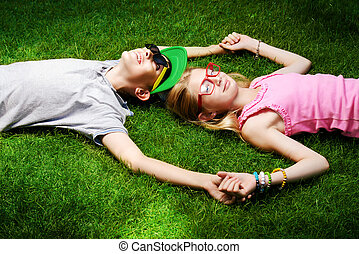 friendship - Two cheerful teenagers on the grass in the...
