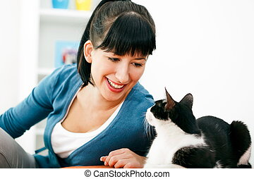 Young woman is having eyes communication with her cat. Selective focus on face.