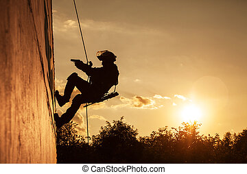 FRIES combat rappeling - Silhouette of police officer during...