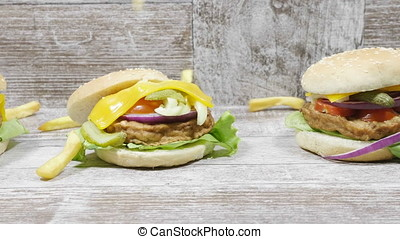 Fries falling over a burger next to cola and ketchup. Fast food cheeseburger made with fresh meet and salad ingredients on a plate.