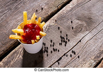 Fries with ketchup and pepper.
