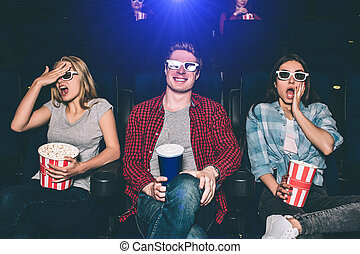 Frightened and worried teenagers are sitting and watching movie. Girls are trying not to see what's going on the screen. Guy is looking straight and smiling.