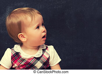frightened baby girl pupil with chalk at a school board