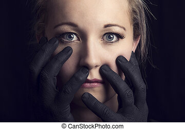 Frightened blonde woman grabbed by black hands on face
