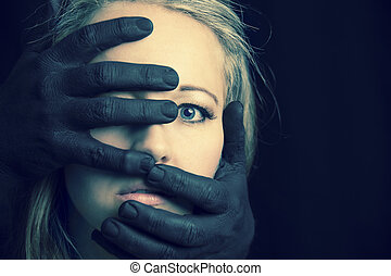 Frightened blonde woman grabbed by black hands on her face artistic conversion