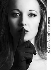 Frightened blonde woman silenced with finger in black on her face artistic conversion