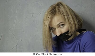 frightened girl gagged sits on the floor. kidnapping and violence