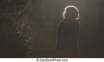 Frightened girl alone in the park at night, street light goes out