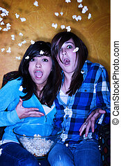 Frightened Hispanic girls with popcorn watching television