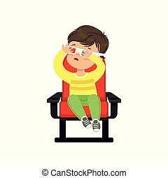 Frightened little boy in 3d glasses sitting on a red chair...