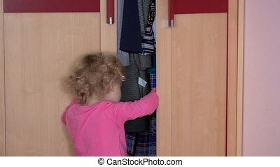 Frightened little girl open closet door and hide inside it....