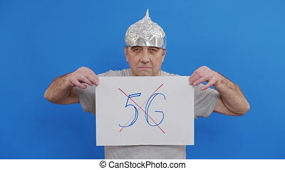 Frightened man in a tinfoil hat waved off the 5G waves.5G tower radiation protection. Irrational fear of a non-existent problem. Protective foil helmet to the brain from aliens