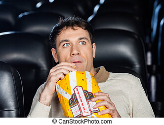 Frightened Man Watching Movie In Theater