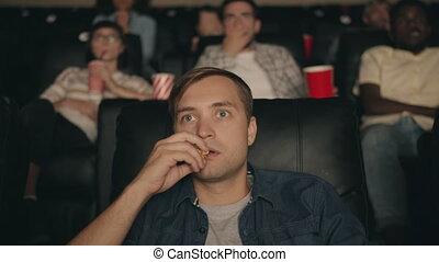 Frightened man watching scary horror film in cinema eating...