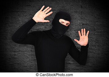 frightened robber raised his hands up on gray background