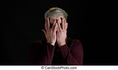 Frightened stylish young man looking camera with scared fearful glance covered face with hands hiding, meeting his own phobia, evidence horror event, fearful freaked out emotions on black background