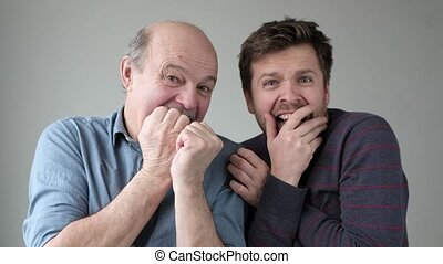 father and son have nervous expressions, keep hands near ...