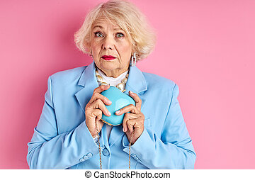 frightened well-off lady with purse in hands, stand in shock scared of something, with wide opened eyes, isolated over pink background