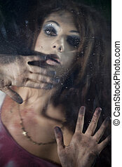 Frightened woman behind the glass - Bloody and scary looking...