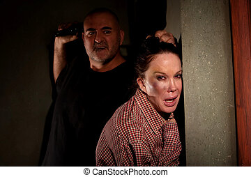 Frightened woman in hallway with menacing man - Woman in...