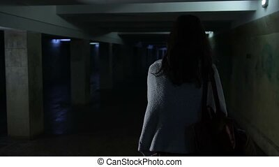 Back view of attractive woman, scared by a stranger, running through dark underground passage . Frightened young girl running away from stranger through underpass at night. Slow motion. Steadicam stabilized shot.