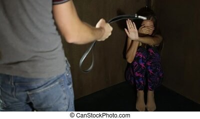 frightened woman sitting in the corner with a faceless man holding a belt, a conceptual shoot portraying the process and effects of domestic violence
