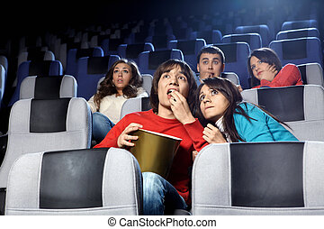 Frightening cinema - The scared young people at cinema...
