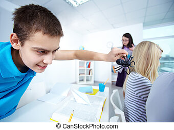 Frightening girls - Evil lad holding black spider and going ...