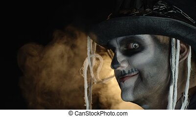 Frightening man in skeleton Halloween makeup turns head and looks into camera with eyes wide open