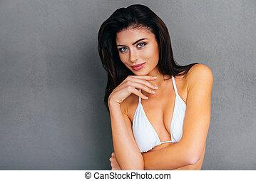 fris, en, beautiful., aantrekkelijk, jonge, glimlachende vrouw, in, witte bikini, holdingshand, op, kin, en, kijken naar van fototoestel, terwijl, staand, tegen, grijze , achtergrond