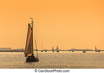 Frisian Dutch sailing ships during sundown - Traditional...