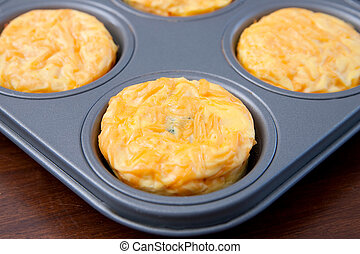 frittata muffins - corner of a silver metal tray with four...