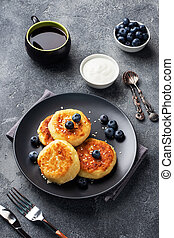Fritters of cottage cheese with blueberries. Cheese curd cheesecakes, pancakes on a dark concrete background. Copy space.