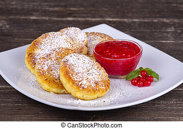 Fritters of cottage cheese with red jam in plate on table, close up