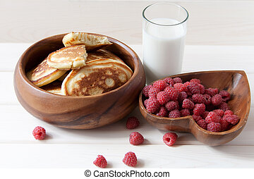 Fritters with a raspberry on wooden plate