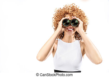 Frizzy-haired gingner girl looking through binoculars