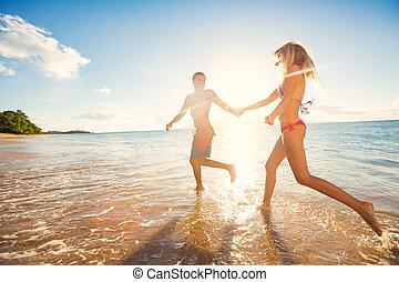 frohes ehepaar, auf, tropischer strand, an, sonnenuntergang
