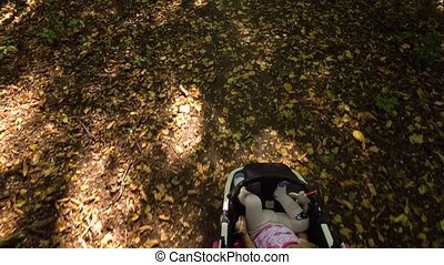 From above of little girl in stroller - From above view of...