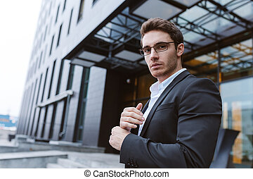 From below image of Business man in glasses standing sideways