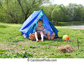 From blue tents on a grassy glade meadow legs stick out and a little boy sitting in it and smile