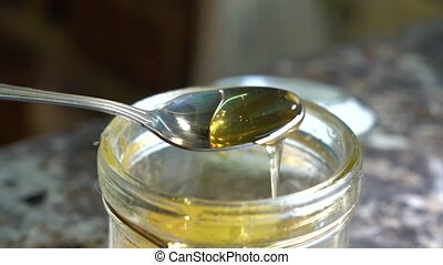 From jars of honey with a spoon scoop the honey, turn the spoon and the honey slowly flows down.