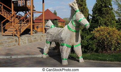 From straw and crop stalks made figurine of a donkey tie up...