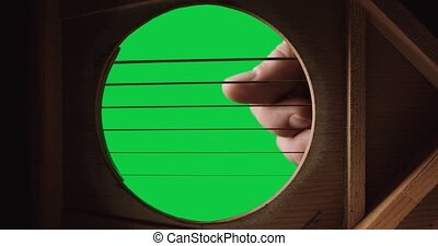 View from inside guitar looking through sound hole with vibrating strings on a green screen chroma key background