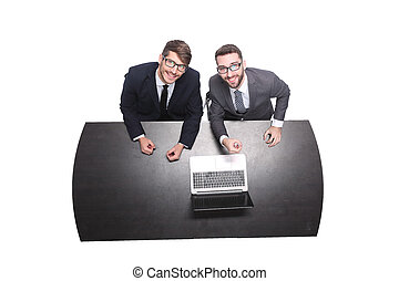 top view. smiling business colleagues sitting in front of an open laptop