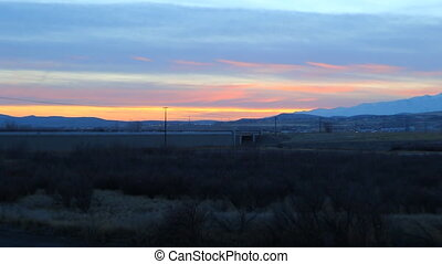 From wide to zoom view of a sunset with evening traffic and mountains in the background